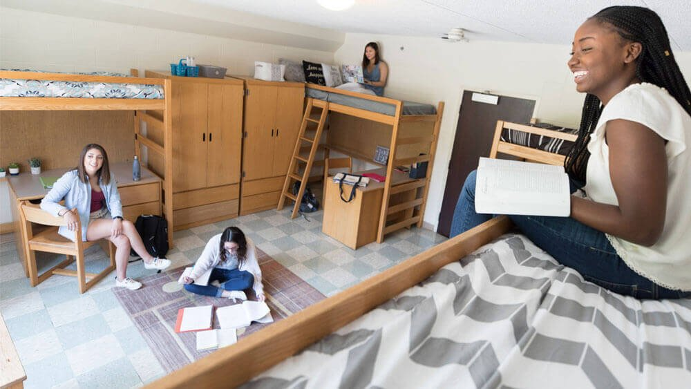 Four students talk in their residence hall room