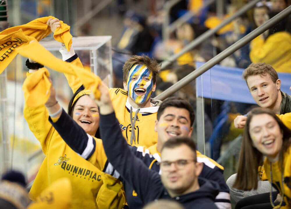 Students in bobcat gold cheer at a hockey game