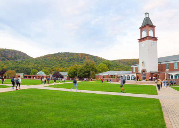 Students walk across the quad with the Sleeping Giant in the background on a beautiful fall day.