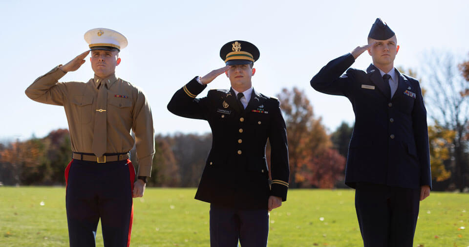 Three veteran students in the school of law salute during a ceremony
