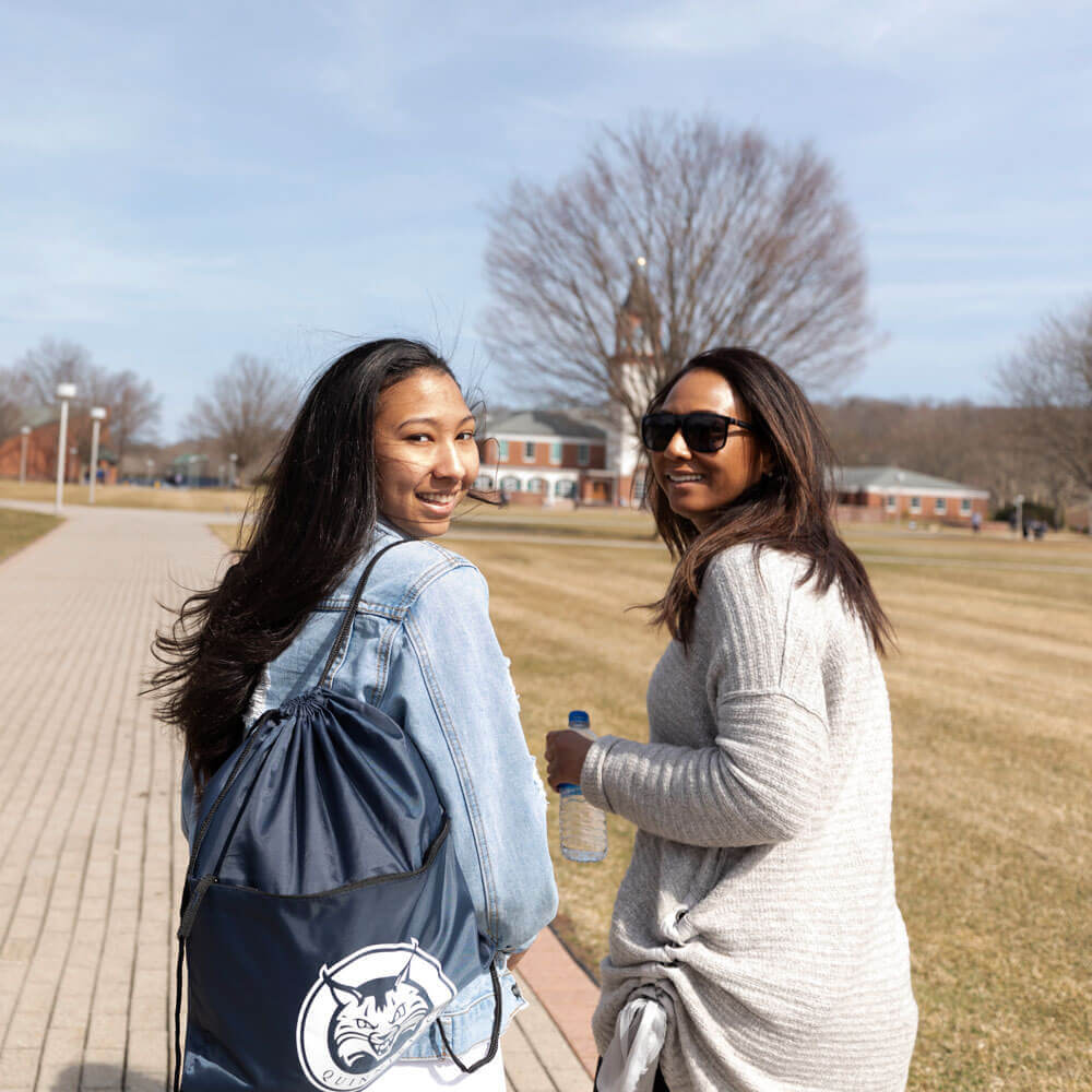 An admitted student and her mom walk along the campus quad