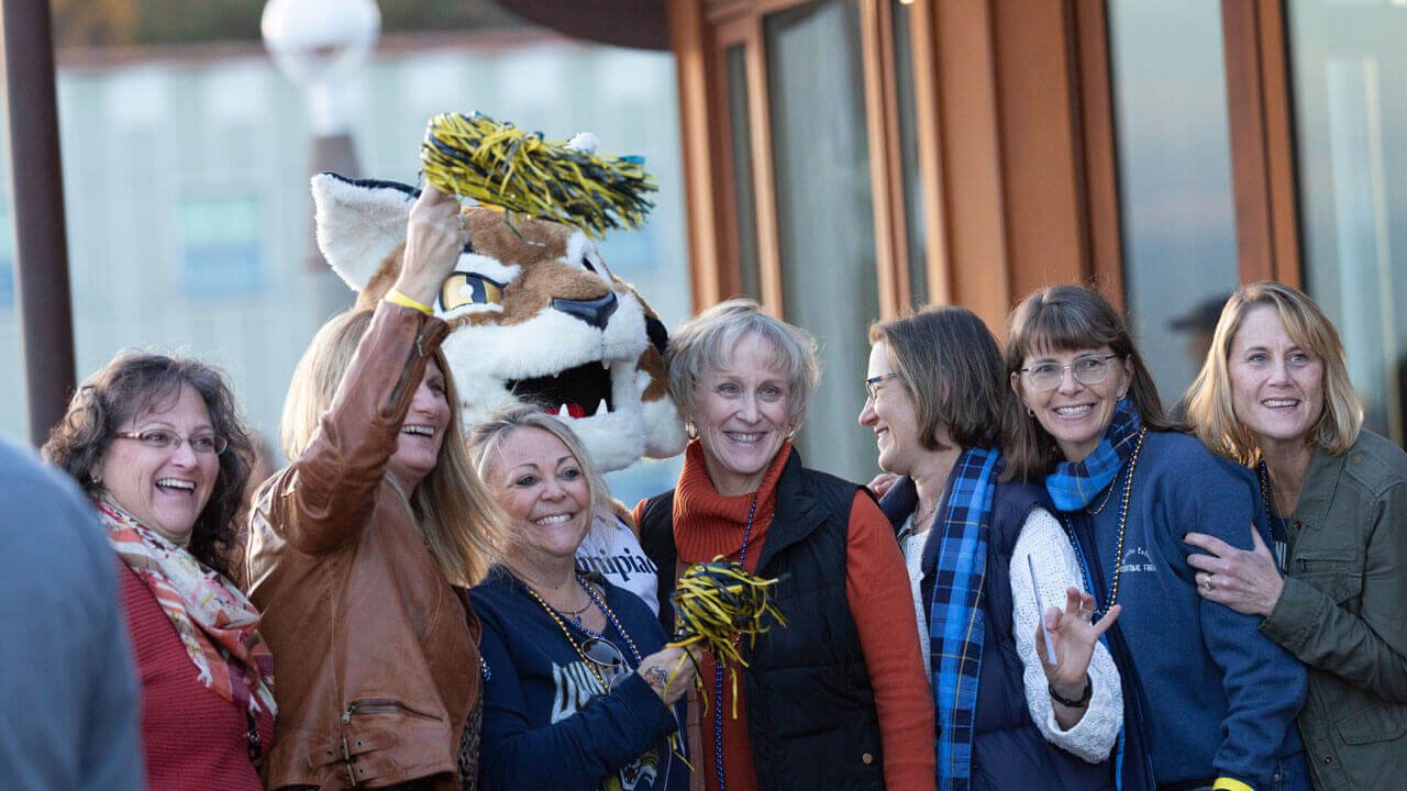 Several alumnae smile for a photo with Boomer the mascot at Alumni Weekend event