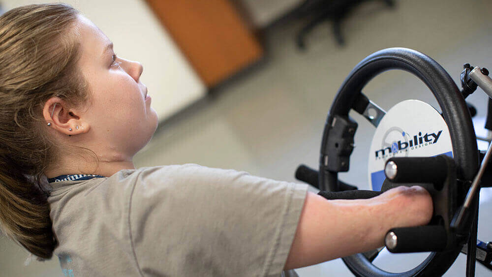 A teenager with limb loss uses a specially-designed steering wheel