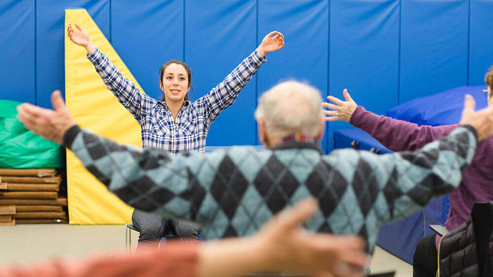 A health sciences student leads a group of senior citizens in stretching exercises