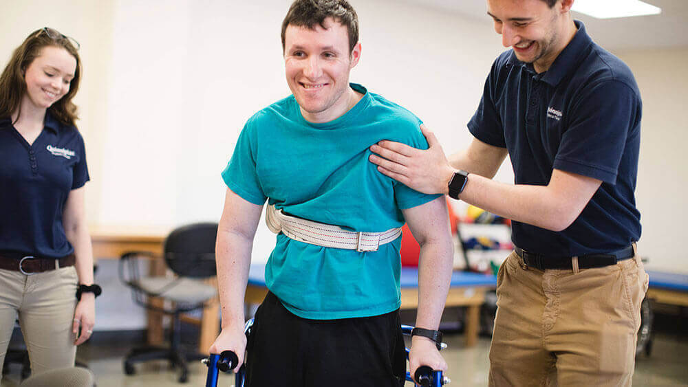 Two health sciences students help a patient walk with his crutches