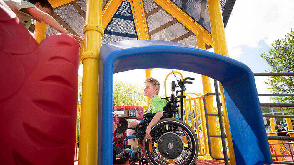 A young boy in a wheelchair plays on a local playground