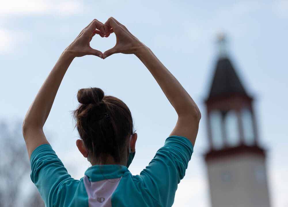 A student forms her hand into a heart with the Quinnipiac clocktower in the background