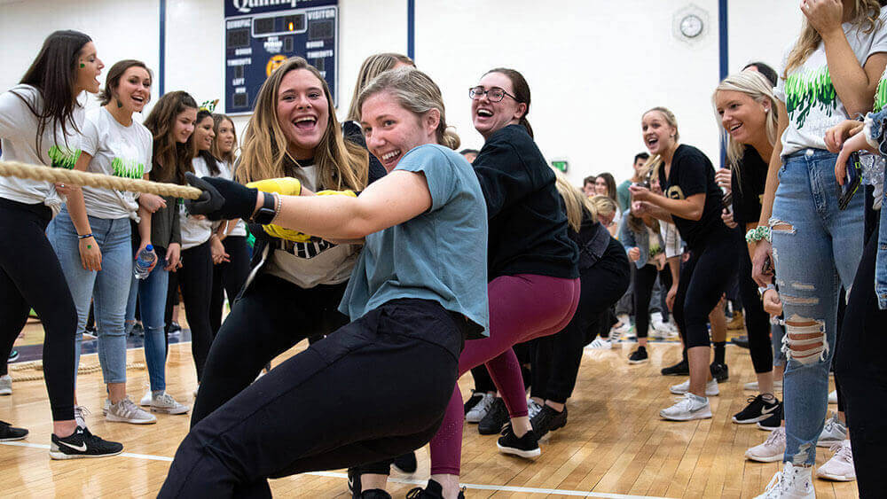 Students compete in a game of tug-of-war for a charity fundraiser