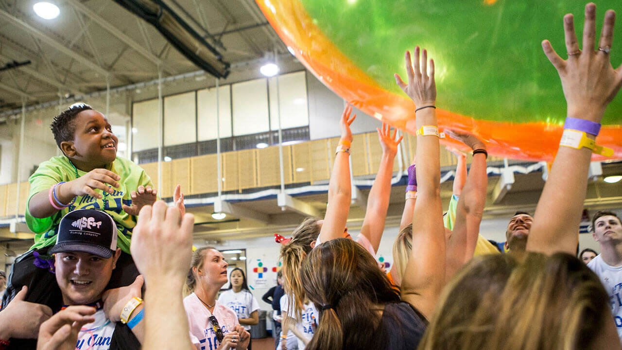 Students hold up giant, colorful beachball