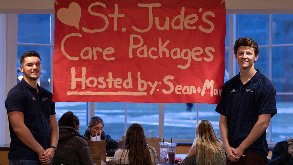 Two Quinnipiac students stand in front of a red St. Jude's fundraiser sign