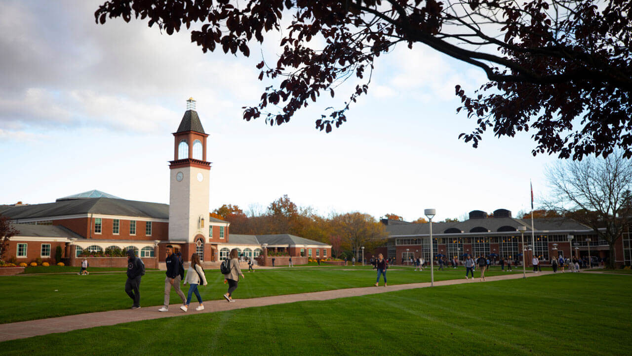 Dozens of students walk across the Quinnipiac quad in the autumn