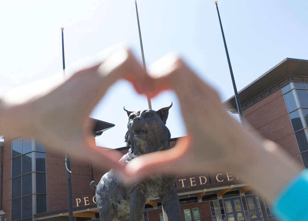 A student forms her hand into a heart with the bobcat statue in the background