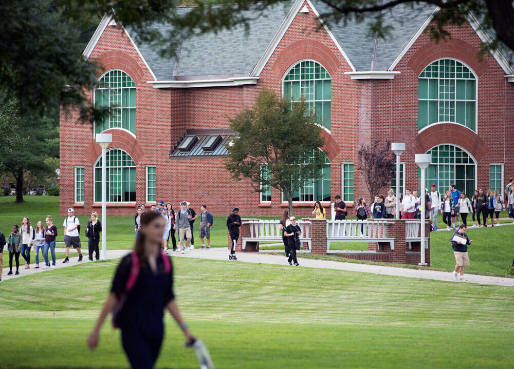 Dozens of students walk across the quad on the Mount Carmel Campus