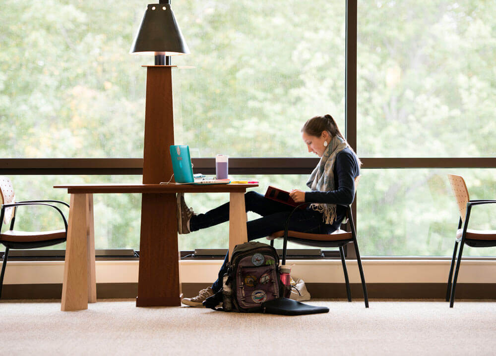 A student studies in front of big windows on the North Haven Campus