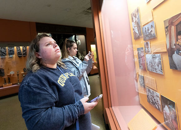 Rachel Houlihan stands with another student looking at a photos and information behind glass at a museum exhibit.