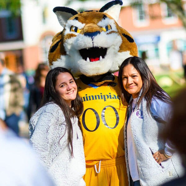 A student and her mother smile next to the Boomer mascot
