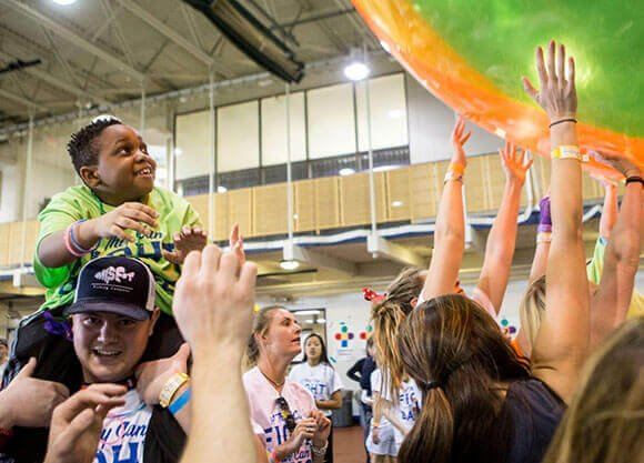 Students hold up a plastic ball as part of QTHON.